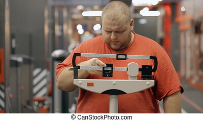 Attractive and overweight man standing on a mechanical scale...