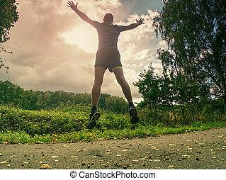 Attractive and tall runner man in slim sportswear running