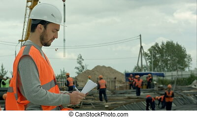Attractive architect is planning to build a construction. He is standing and holding a blueprint
