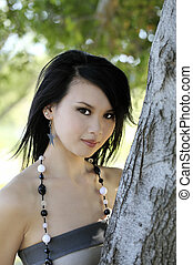 Attractive Asian American Woman Outdoors Against Tree