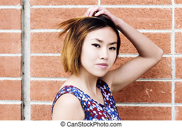 Attractive Asian American Woman Portrait With Brick Wall