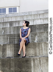 Attractive Asian American Woman Sitting In Dress