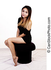 Attractive Asian American Woman Sitting On Stool In Dress