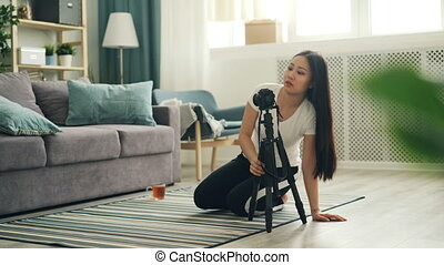 Attractive Asian blogger is installing camera on tripod and...