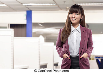 Attractive asian business woman standing in front of desk