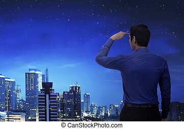 Attractive asian businessman looking at city