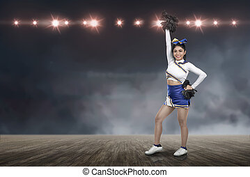 Attractive asian cheerleader holding pom-poms with spotlights on background