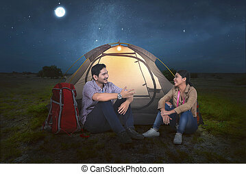 Attractive asian couple relaxing in front of the tent