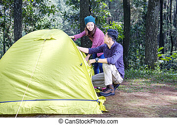 Attractive asian couple set-up a tent for camp