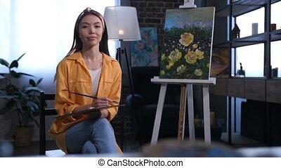 Attractive asian female artist sitting near canvas -...