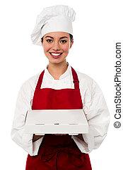 Attractive asian female chef delivering pizza