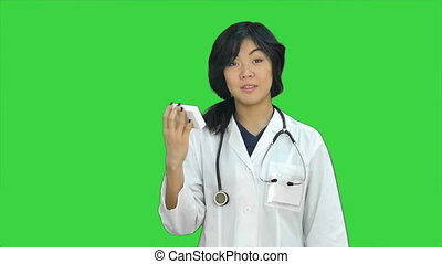 Attractive asian female doctor in lab coat with stethoscope...
