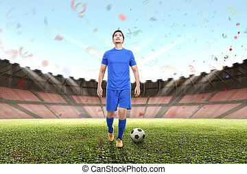 Attractive asian football player man celebrating victory