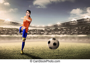 Attractive asian footballer woman kicking ball during match