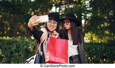 Attractive Asian girl is taking selfie with her Caucasian friend after shopping day holding bags and using smartphone. Modern lifestyle, technology and youth concept.