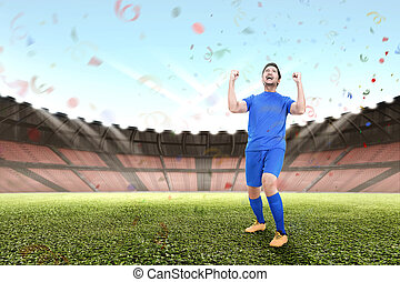 Attractive asian male football player celebrate victory