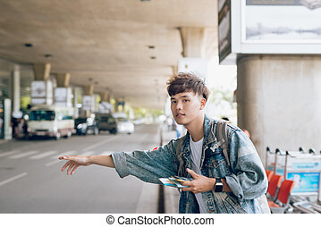 Attractive asian man calling a taxi at the airport