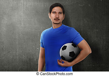 Attractive asian soccer player holding the ball