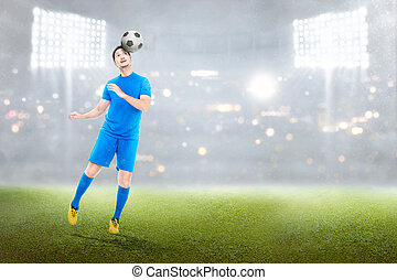 Attractive asian soccer player in action with the ball