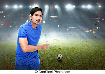 Attractive asian soccer player man running with ball