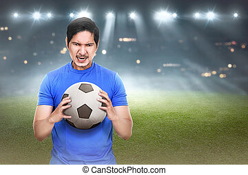 Attractive asian soocer player with ball on his hand
