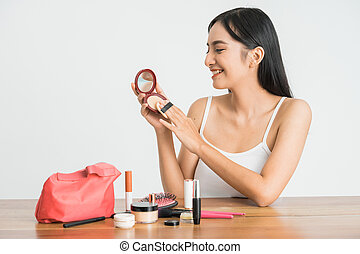 attractive asian woman applying face powder