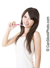 Attractive asian woman brushing teeth