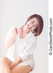 Attractive Asian woman drinking at home, lifestyle concept.