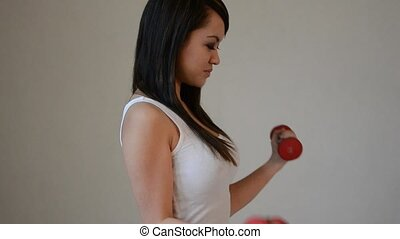 Attractive asian woman exercising with dumbells