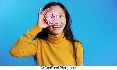 Attractive asian woman having fun with donut. Girl showing ...