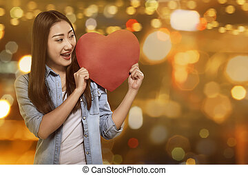 Attractive asian woman holding red heart