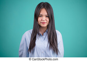 Attractive asian woman posing isolated on blue background -...