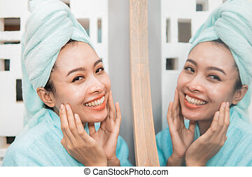 attractive asian woman standing in front of mirror with towel