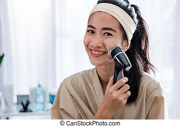 woman using electric facial cleanser machine