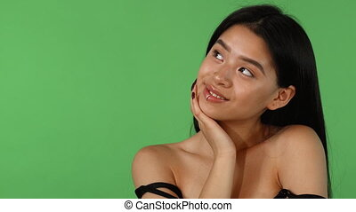 Attractive Asian young woman posing dreamily on green...