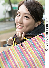 Attractive Asian young woman shopping and holding bags