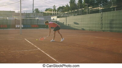 Attractive Athlete Poses Near Net In Tennis Court. Young athletic female playing tennis, walking in an indoor court, woman player become on a game position, training day. High quality 4k footage