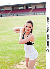 attractive athletic woman during a shot put training in a stadium