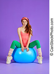 attractive athletic woman sits on blue fit ball with legs apart