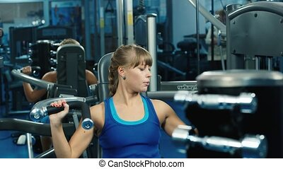 Attractive athletic woman training on a fitness trainer