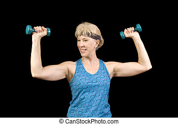 Attractive baby-boomer exercising with weights isolated over...