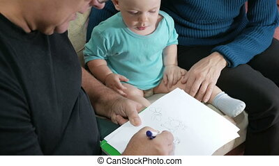Attractive baby boy draws a pen with his grandparents home on the couch. The boy stares at the animals that drew grandfather. The concept of different generations