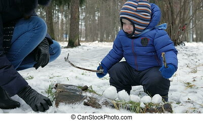 Attractive baby playing with mother in the winter outside in the woods. Mother molds for snowballs year-old boy