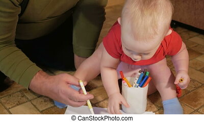 Attractive baby sitting on the pot and drawing with her...