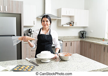 Attractive Baker Holding Pastry Bag While Making Eye Contact