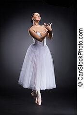 attractive ballet dancer standing and smiling. beautiful ballerina standing tiptoe and practicing