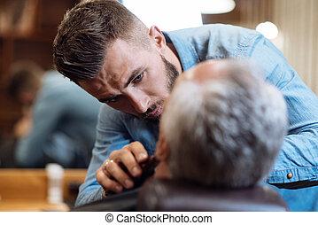 Attractive barber shaving beard of senior man