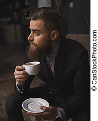 Attractive bearded businessman is resting in cafeteria