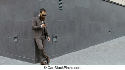 Attractive bearded businessman looking around and using his...