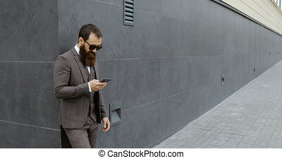 Attractive bearded businessman looking around and using his smartphone while staying out of the modern building,